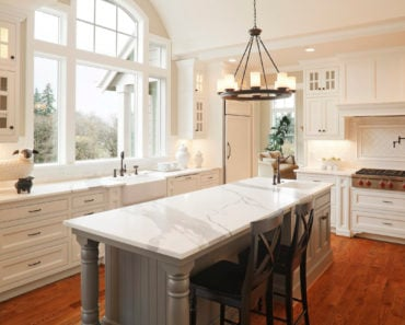 Gray kitchen island base with marble surface in white kitchen