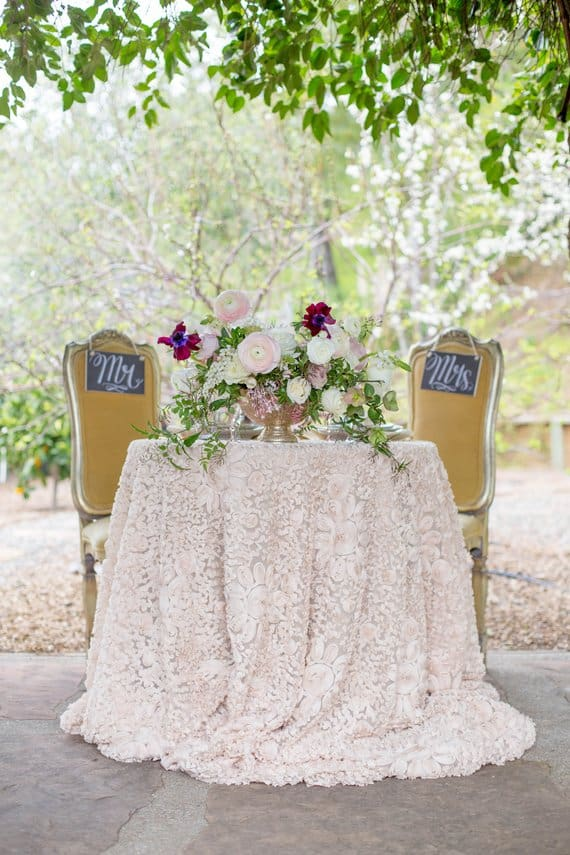 Lace fabric used as tablecloth on the newlywed's table at a garden wedding setting.
