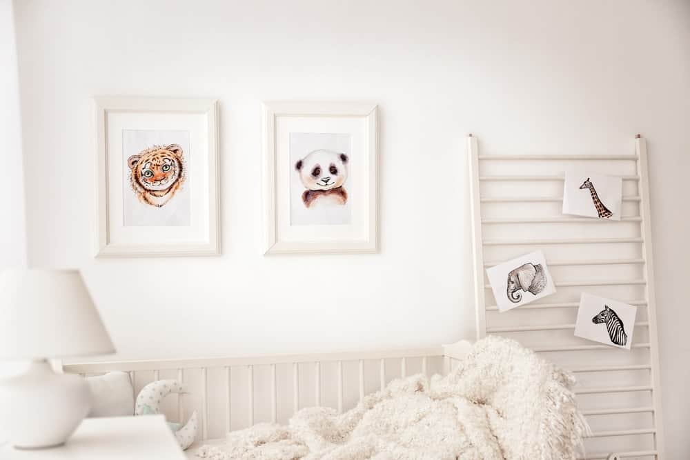 White nursery room with picture frames and a ladder with pictures of animals.