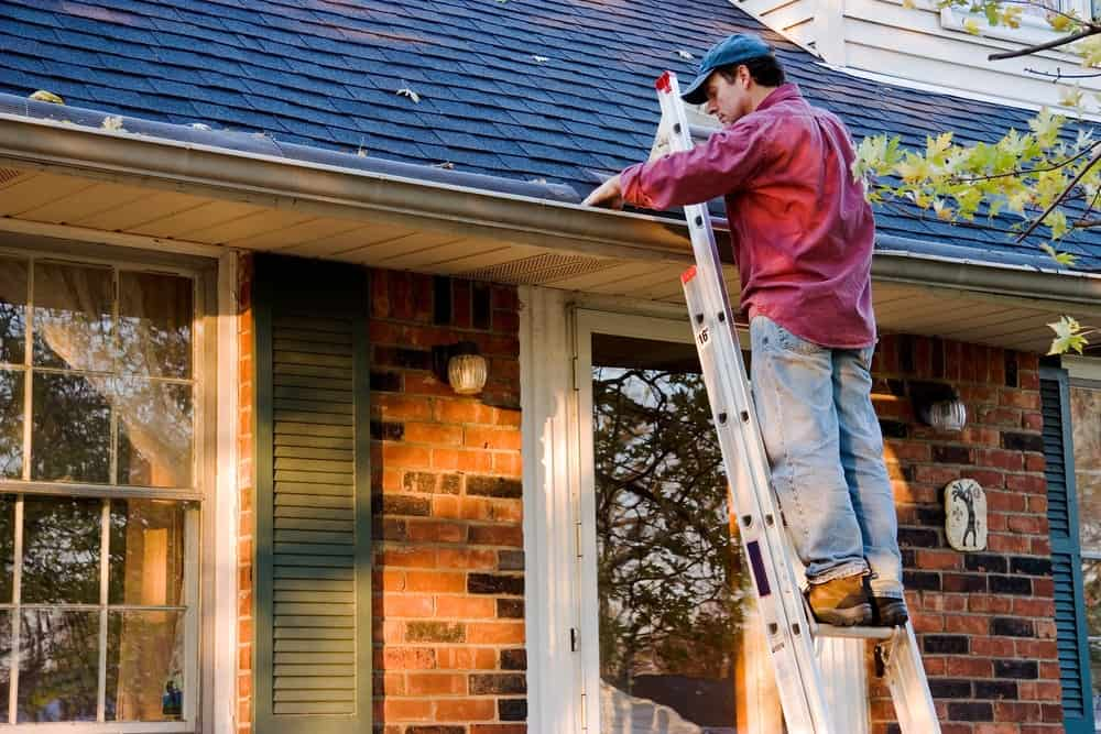 The man is using a ladder to clean the gutter of a contemporary home.