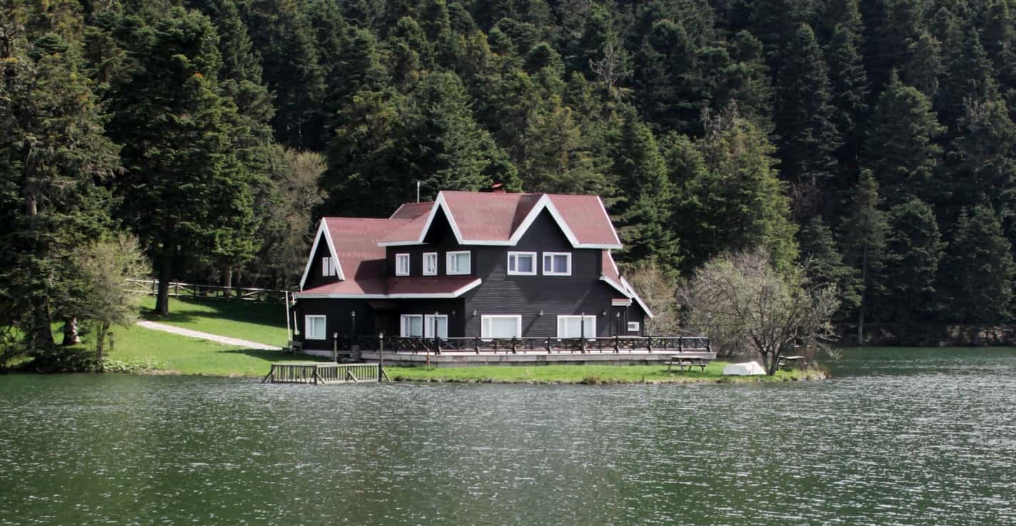 Crisp white outlines this lake house's roof peaks and windows. The white trims also stand out against the red roof and dark wood siding which can easily blend into the green scenery.