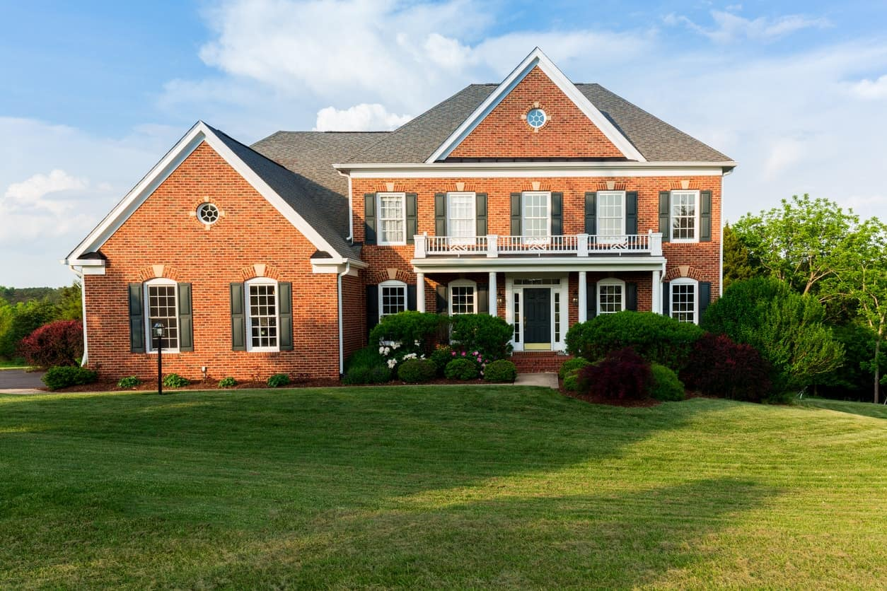 The dark roof and shutters combine with the red brick exterior for a rustic look. White trims add bright contrast to this large family house.