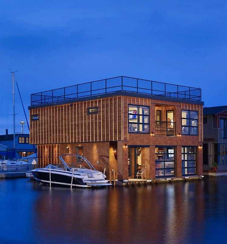 A large floating home featuring a wooden exterior and a roof top.