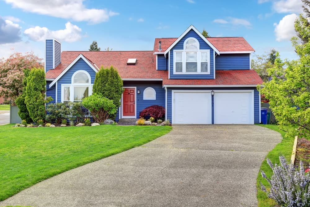 The combination of a red roof, blue exterior, and crisp white trims create a playful look for this suburban house.