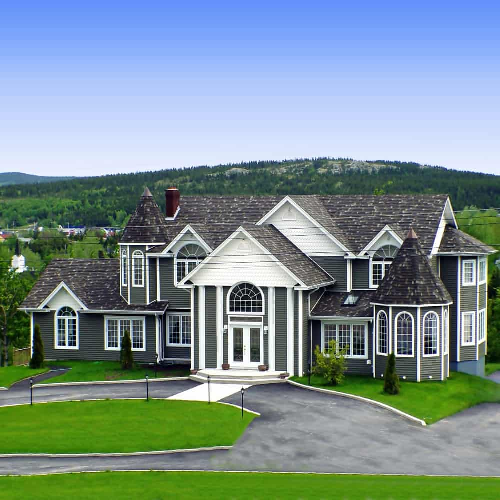 The dark shingles and mossy green exterior siding can make this large luxury house recede into its green surrounding. White trims serve as its saving grace as it makes the house stand out against the background.
