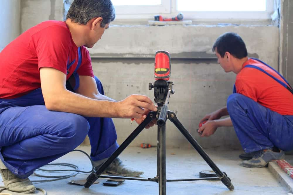 Two construction workers are using the laser level to determine the suitability of the cement application.