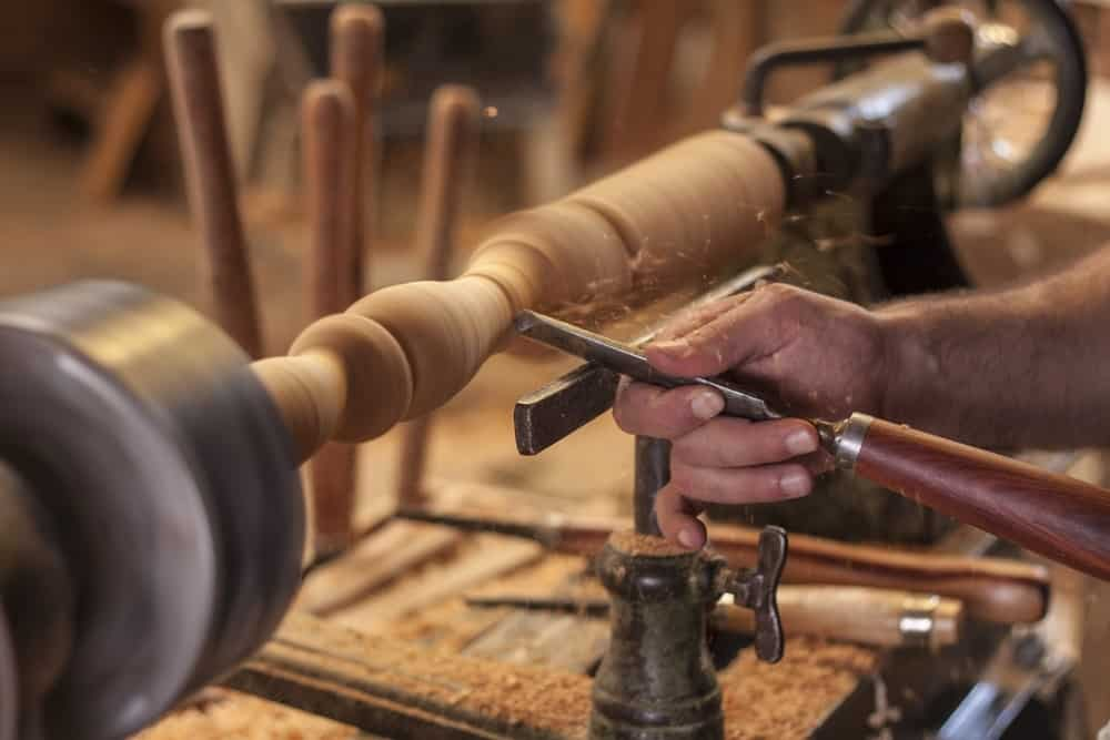 A woodworker uses a lathe to shape a piece of wood.