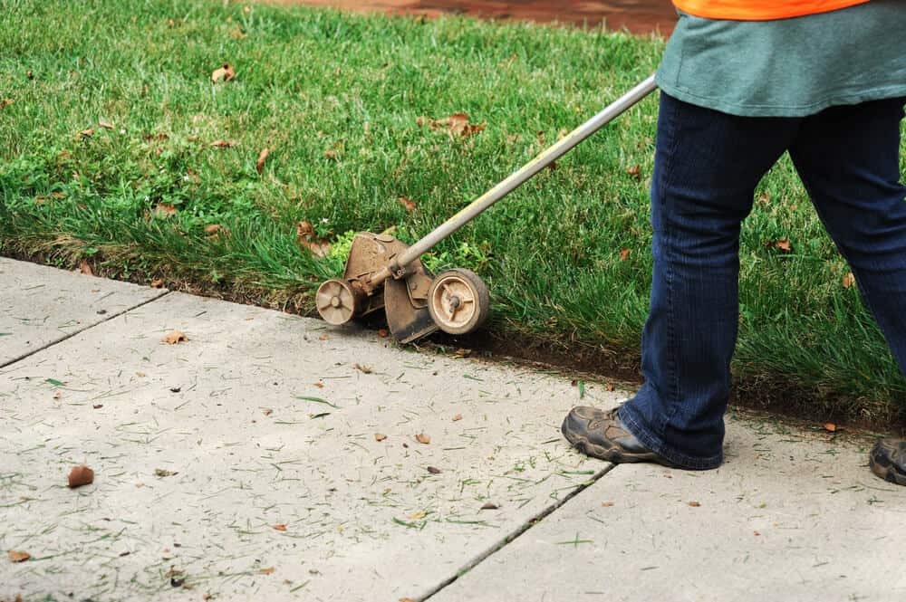 A man maintaining and trimming the edges of his lawn.