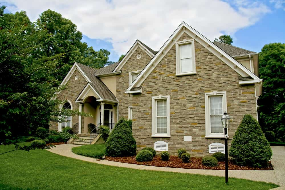 A lovely stone house with double-hung windows. The white soffit, window and door trims give this house a fancy yet minimalist finish.
