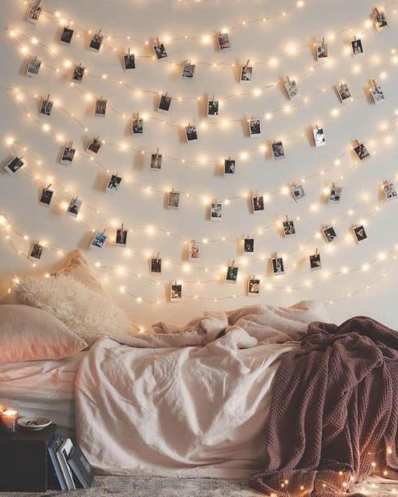 Polaroid films clipped on string lights against a wall and beside an empty bed.