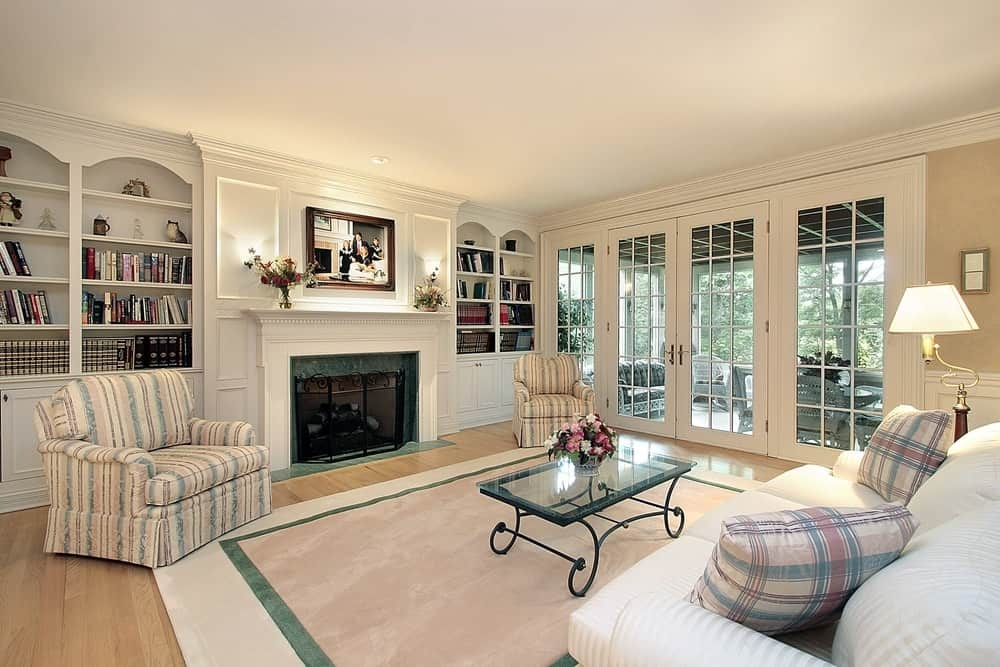 A large white living room with fine art decor and built-in shelving and a fireplace.