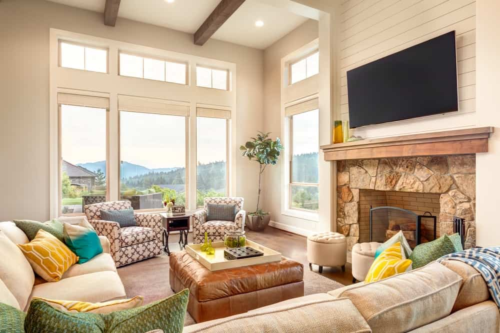 Beautiful living room with beam ceiling, shiplap wall panels, a flat screen TV above a stone fireplace, a beige sectional with multi-colored throw pillows, an ottoman coffee table, and large windows with stunning views.