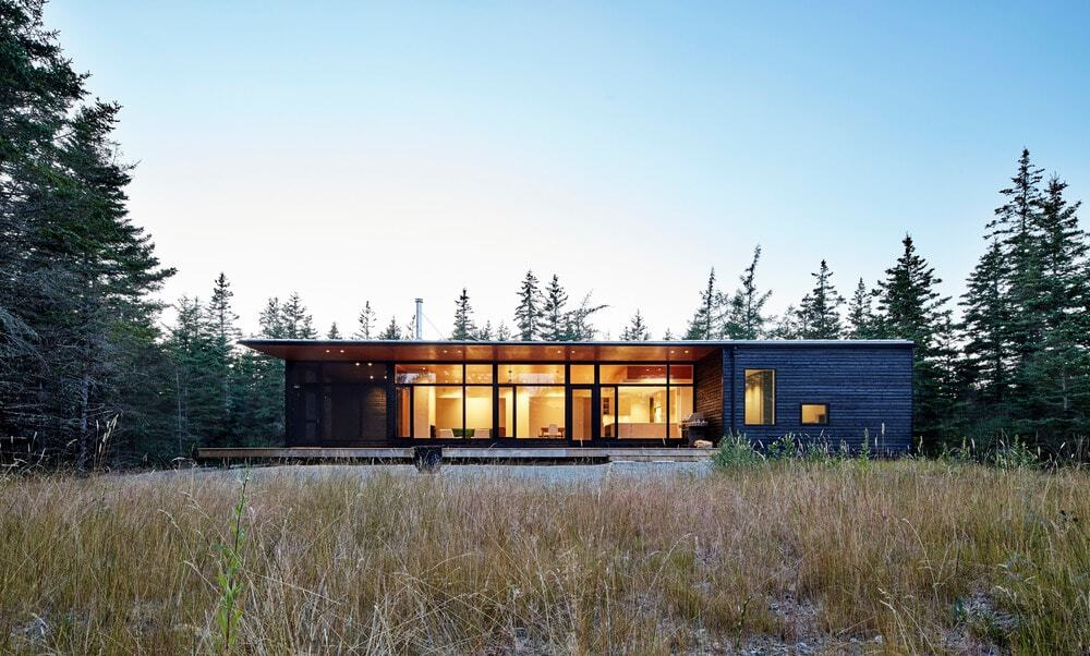 A beach house with a modern interior and exterior design. It is surrounded by tall and mature trees.