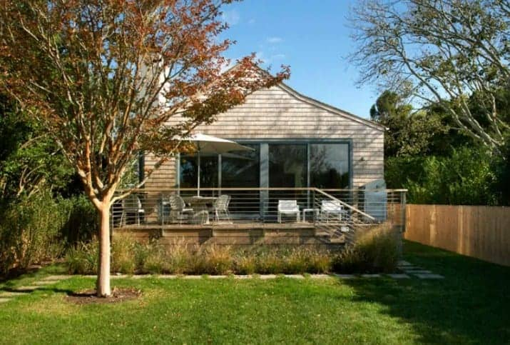 A cottage house with a wooden exterior and glass doors. It has a nice patio area along with a well-maintained lawn area with a walkway.