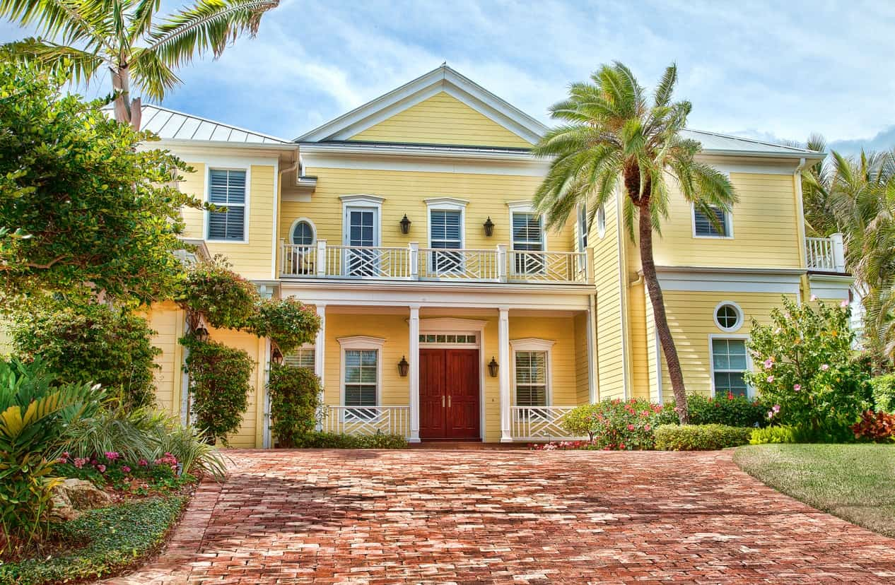 White trims make the sunny yellow exterior stand out while the red double front doors add a touch of warmth. The brick walkway leading to this luxury beach house's entrance add a rustic effect.