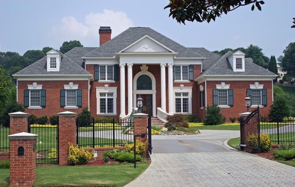 Luxurious suburban colonial mansion with spacious brick driveway.