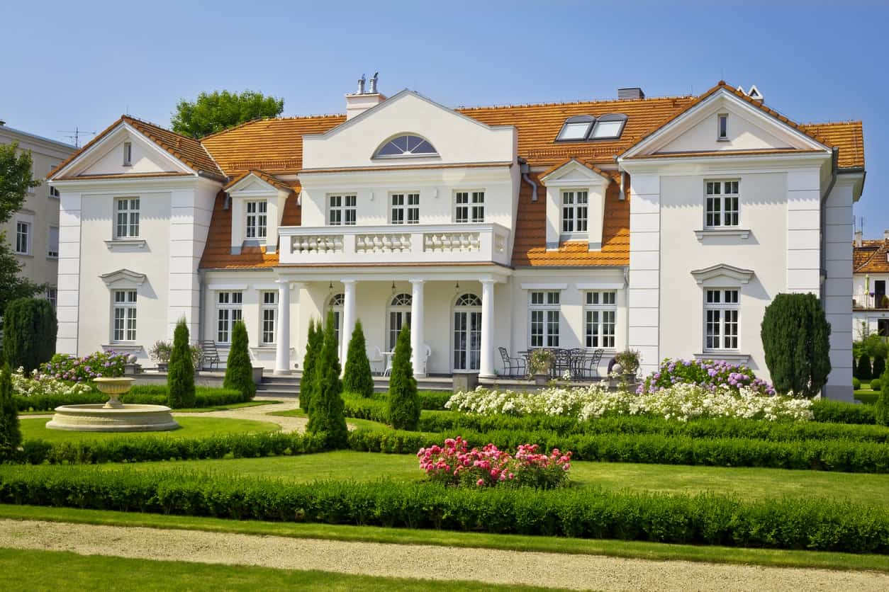Crisp white trims combine with beige exterior for a polished, neat look. The vibrant orange roof shingles inject a dose of visual energy into this mansion.