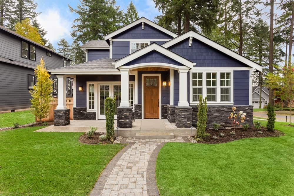 Blue exterior siding and stone brick foundation create a textured look to this luxury house. White trims emphasize the house's outlines and make it appear taller and wider.