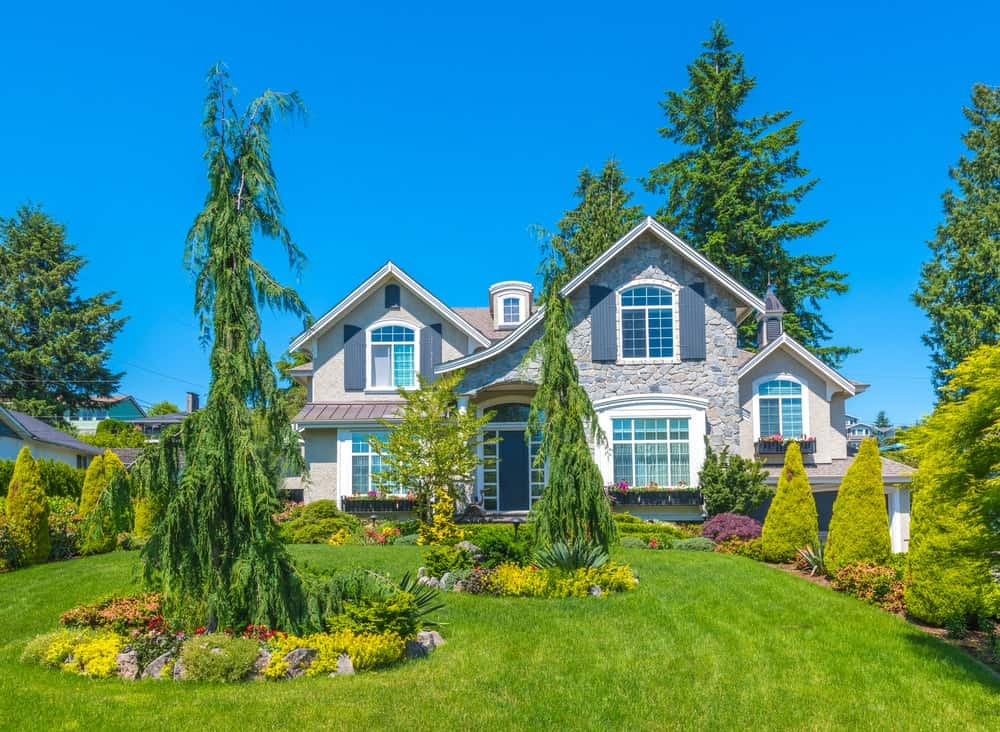 This luxury house's stone exterior makes it blend with its green surrounding. Blue shutters, window sashes, and front door combine with crisp white trims for a refreshing look.