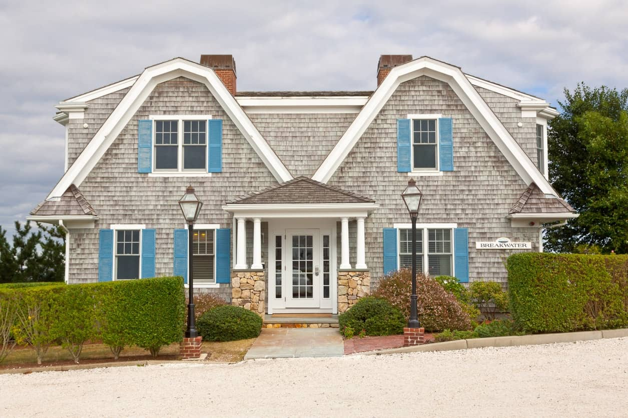 This house's gray brick exterior gives it character and a textured look. Bright blue shutters bring a fresh contrast to the facade's worn-out appeal while white trims tie the overall look together.