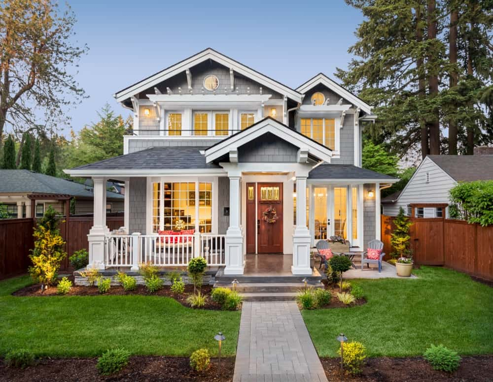 Gray exterior siding creates a soft but chic appeal while crisp white trims heighten the house's architectural features.