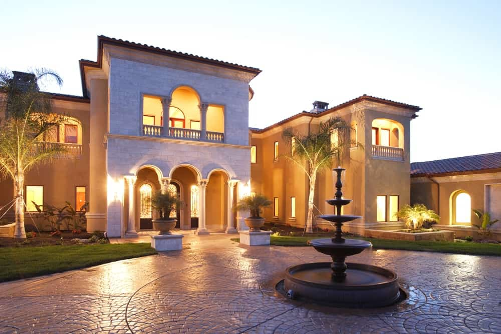 Luxury residential house with central foundation in a circular brick driveway.