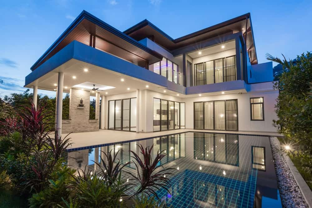 Two-storey luxury villa house with swimming pool and recessed lights.