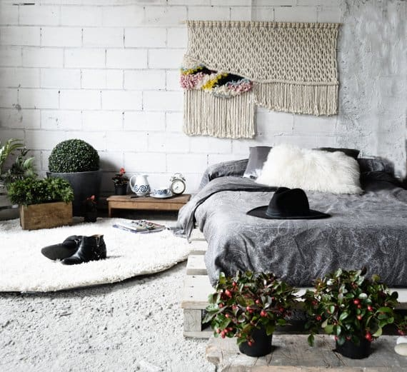 Scandinavian bedroom with whitewashed exposed brick wall, hanging macrame as headboard, carpeted flooring, and indoor plants.