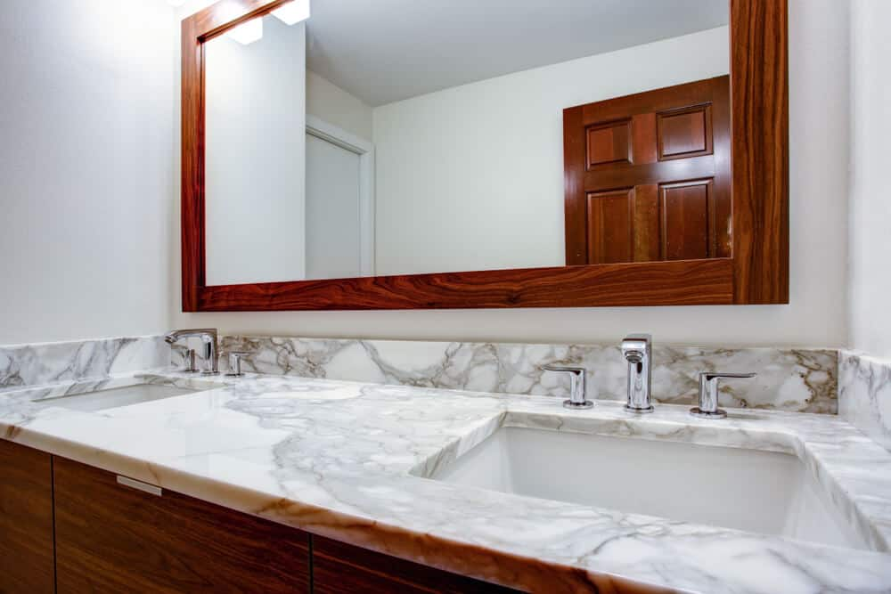 Rectangular vanity with a marbled surface.
