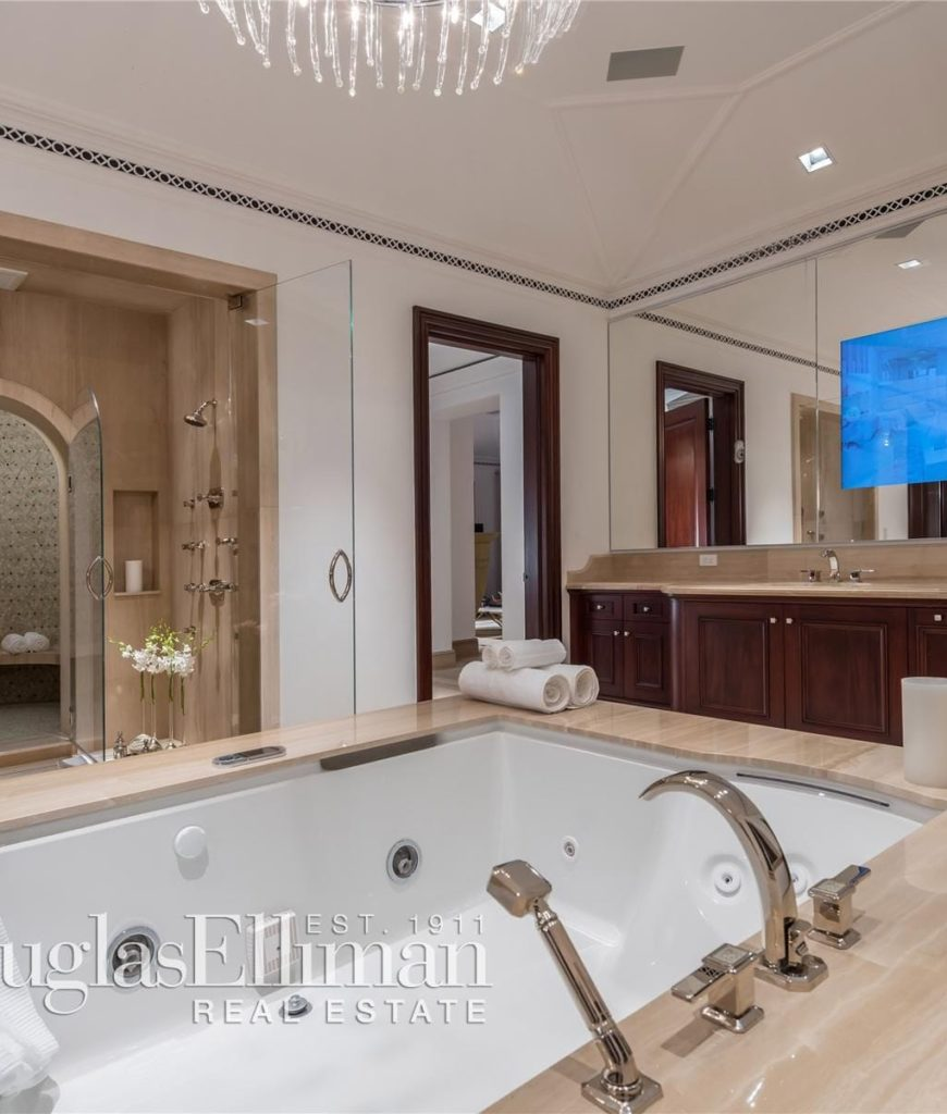 Another view of the bathroom focusing on the soaking tub, chandelier and a wide TV on the mirror.
