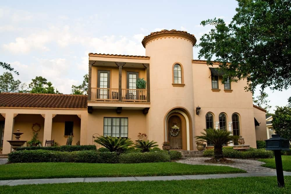Mediterranean-style stucco house with front lawn garden and pavestone walkway.