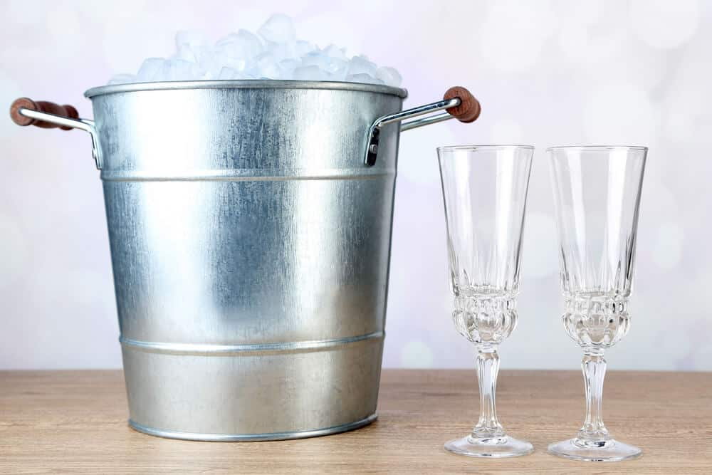 A metal ice bucket with wine glasses on the side.