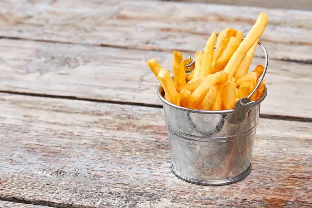 A small metal bucket with french fries.