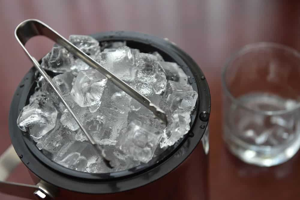 A metal bucket of ice with a metal tong included.