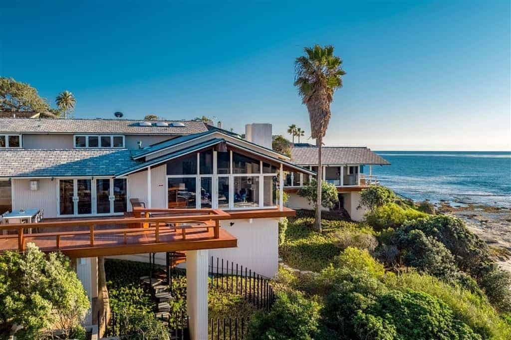 A sprawling mid-century modern beach house with a wooden exterior and a stylish wooden balcony deck.