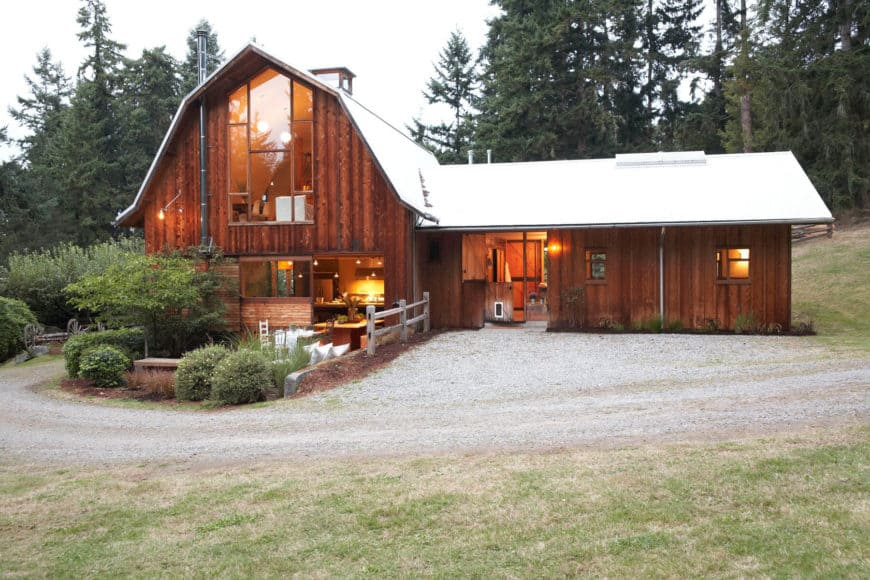 A minimalist guest-oriented barn with a rich wood exterior and warm white lights on the interior.