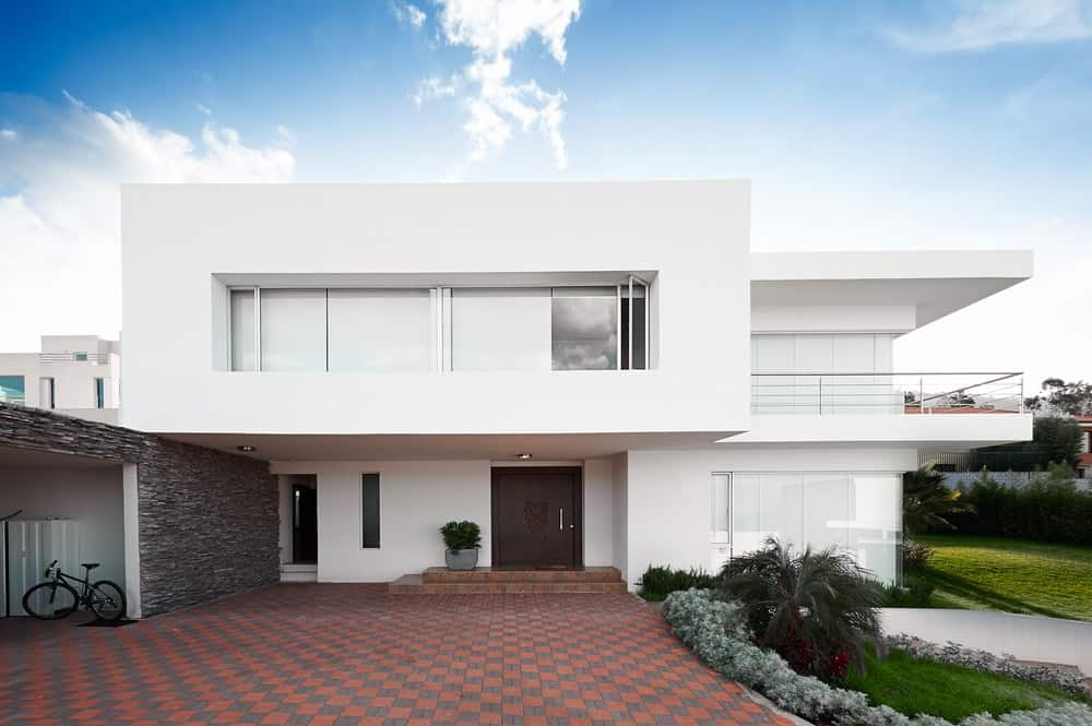 Modern white mansion featuring a geometric style of architecture and a spacious brick driveway.