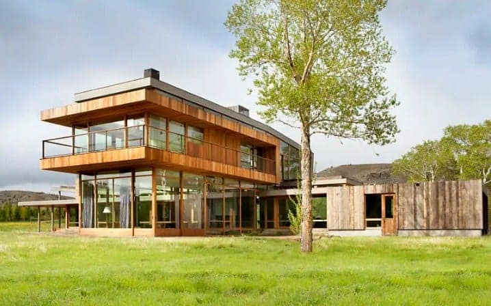 Large modern riverside home with a timber exterior and a peaceful lawn area.