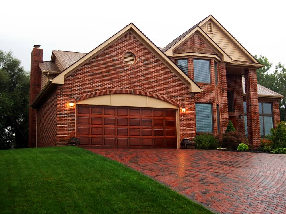 Luxurious brick mansion with pointed roofing and brick driveway.