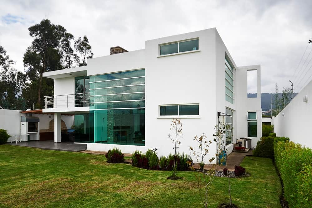 Modern house with glass windows, green field backyard, and flat roofing.
