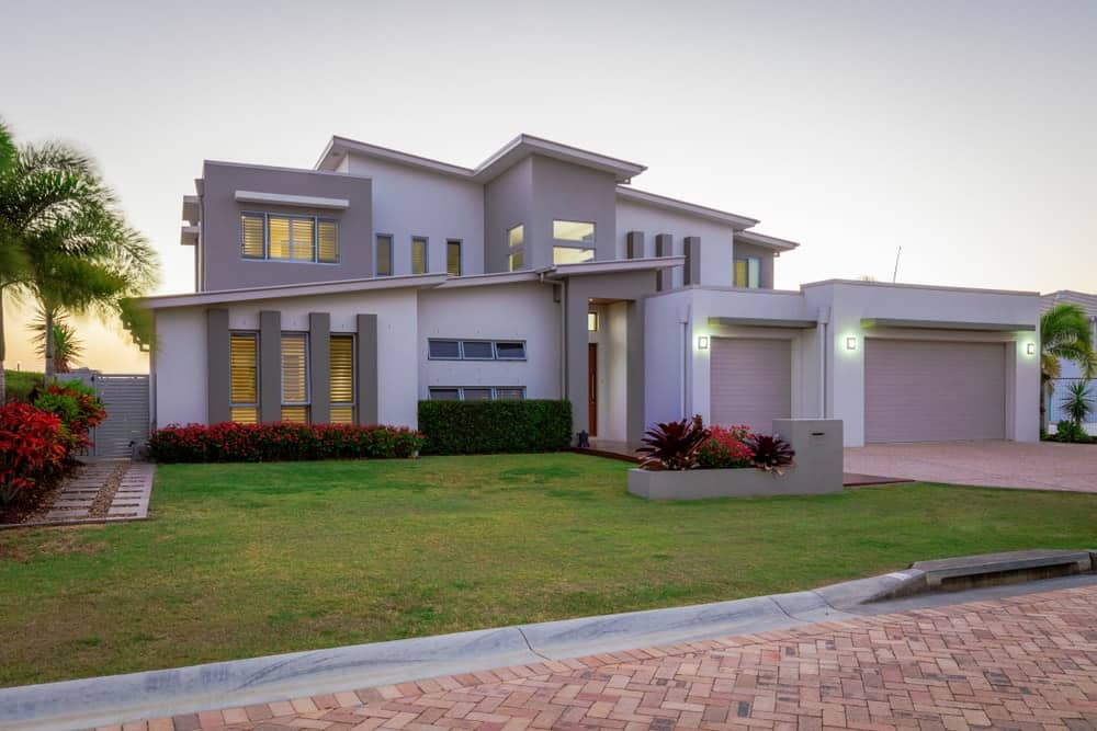 Modern multilevel house with sloping roof, front lawn, and integrated garage.