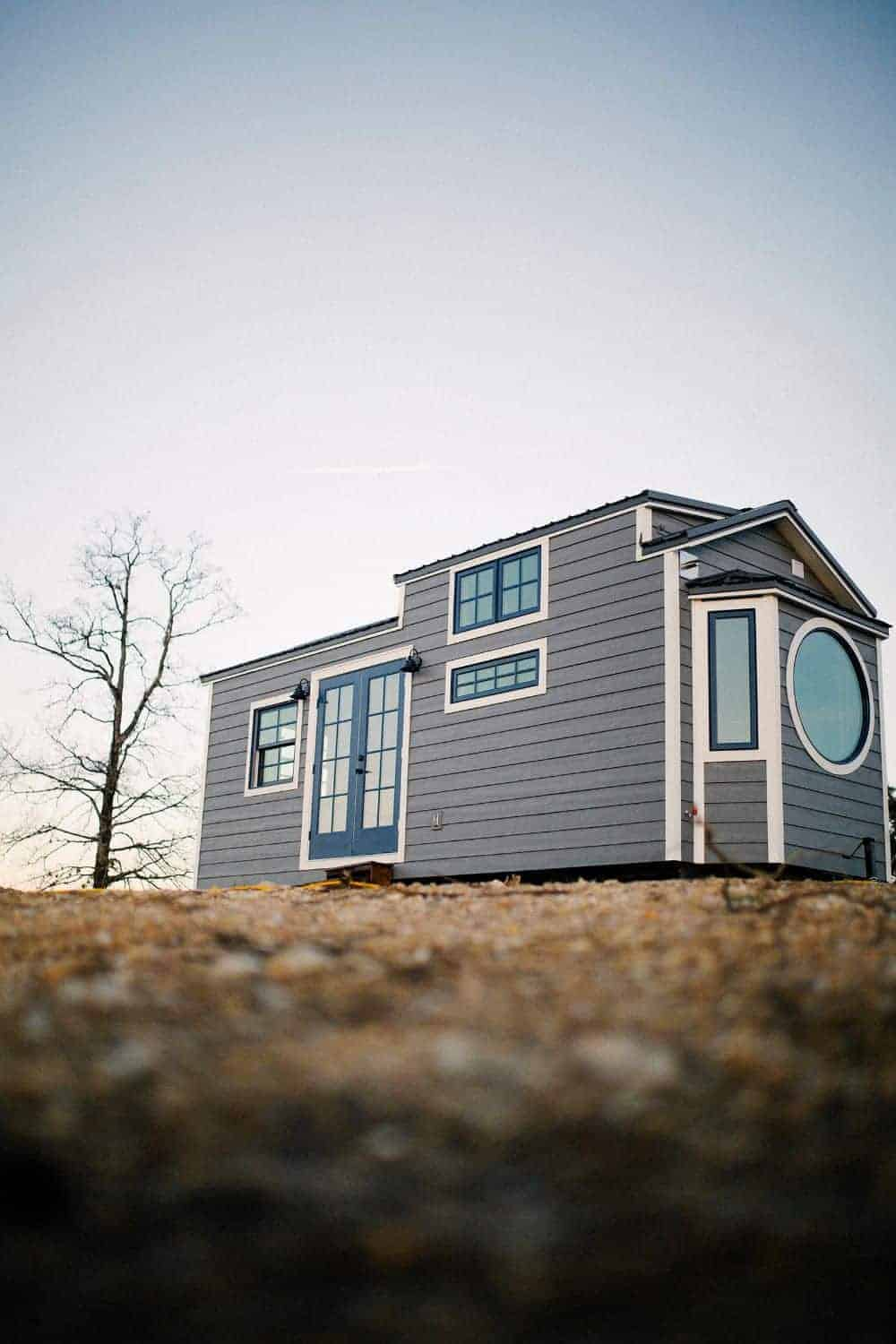 A gray tiny house with a monocle style window.
