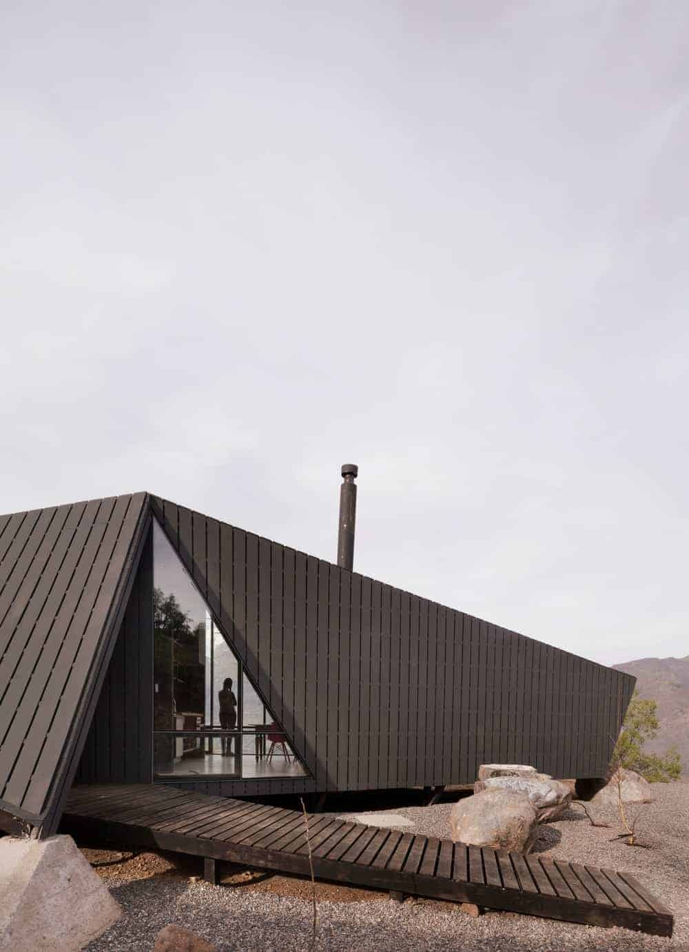 A wooden mountaineers refuge painted in black.