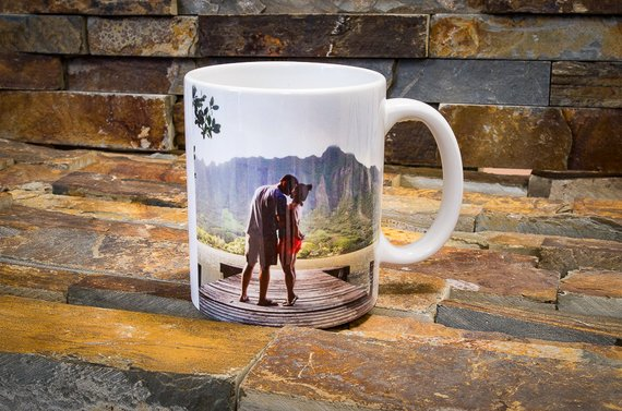 A personalized mug rests on a stone brick surface.