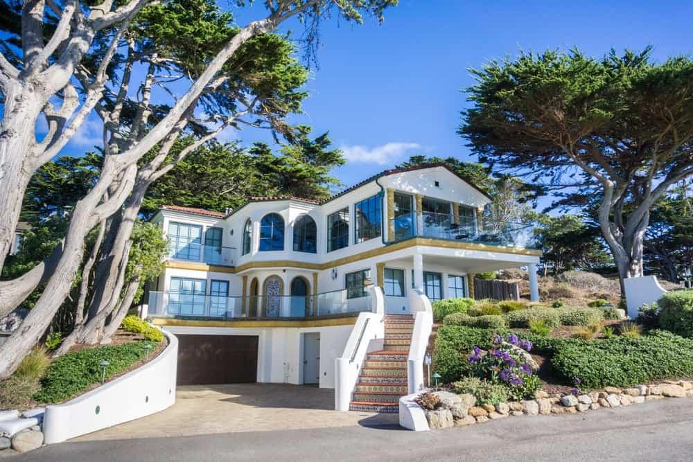 Multilevel house with wide entryway, spacious outdoor area, and contemporary facade.