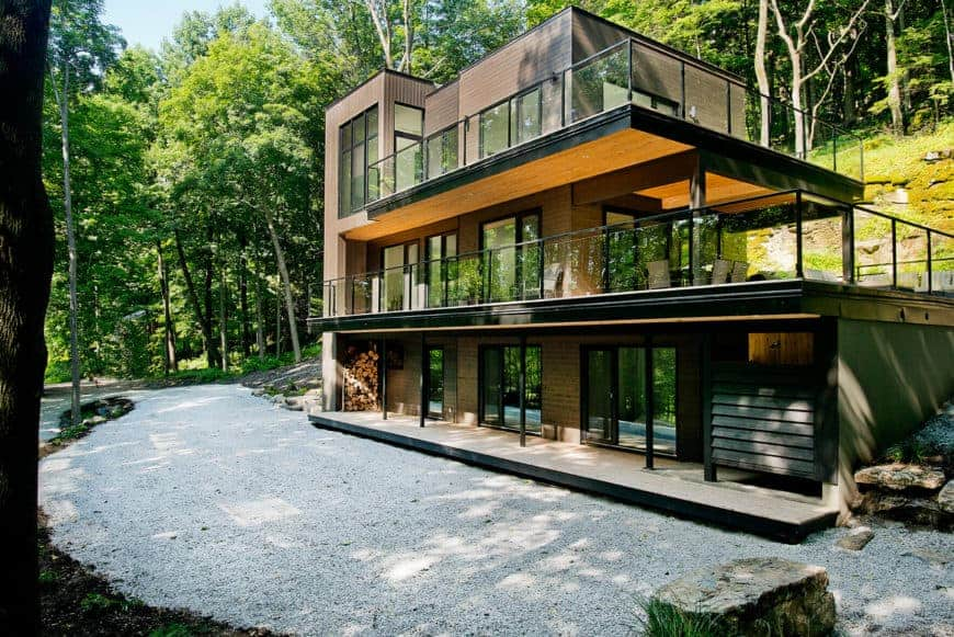A modern house with glass windows and doors. It offers peaceful balconies overlooking the surroundings.
