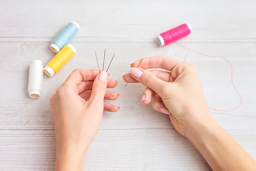 Needles and threads of different colors are needed to make quilts.