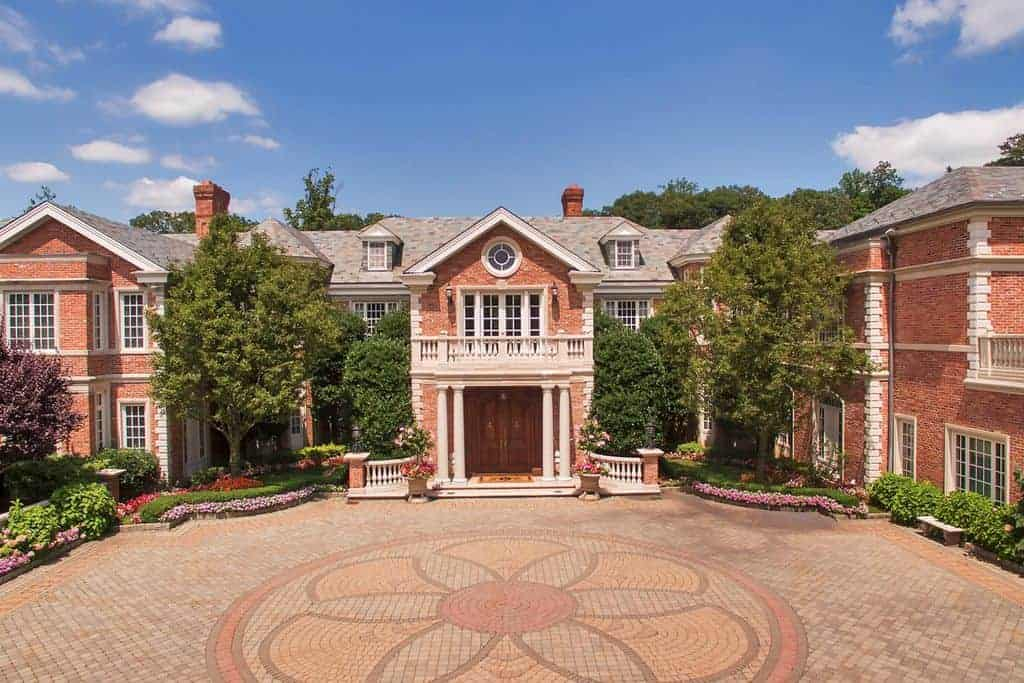 This mega-mansion boasts a beautiful courtyard with a decorated ground area a red exterior.