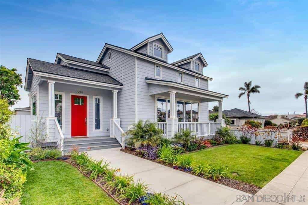 A newly built luxury craftsman home with a wooden exterior painted in gray.