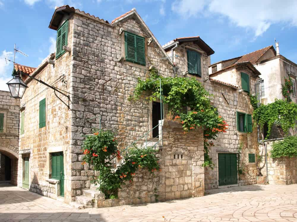An old, historic house with a stone exterior complemented with dark green window frames. Its weathered structure, together with the vines and plants crawling upon its walls, give this house a nostalgic finish.